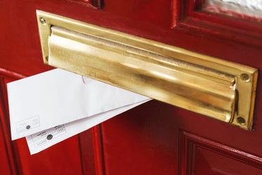 mail peeks out from a brass letterbox