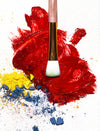 makeup brush lays on vibrant red lipstick color