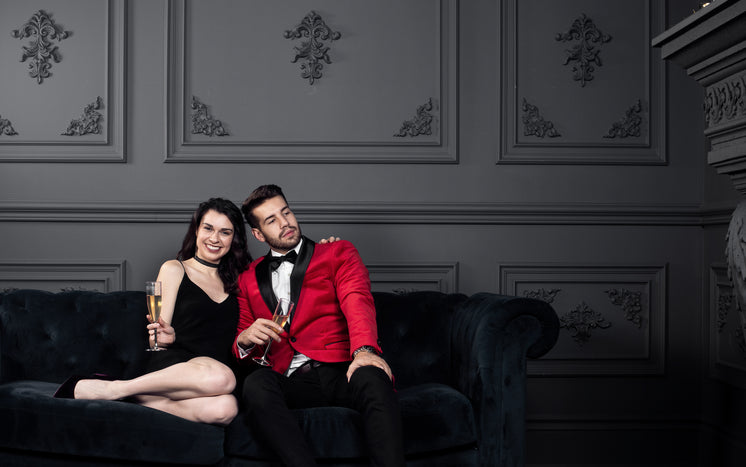 Man And Woman In Fancy Dress Pose On Couch