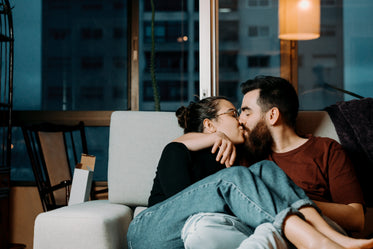 man and woman share a kiss sitting on grey couch indoors