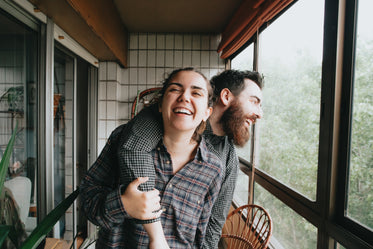 man and woman smile together standing in a solarium