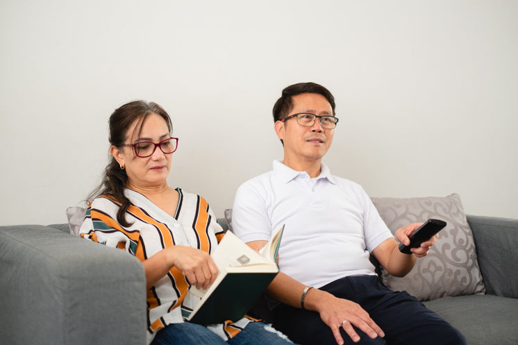 Man And Woman Together Sitting On Grey Couch