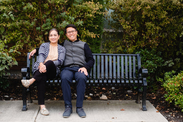 man and woman together smile on park bench