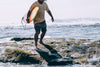 man carrying surfboard emerges from ocean waves