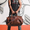 man clutching his leather duffle bag