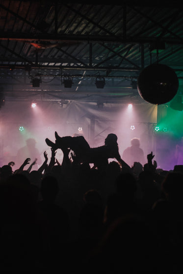man crowd surfing in dark club