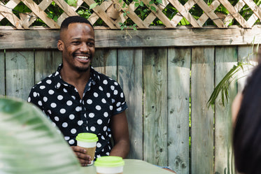 man drinking coffee in polkadot shirt