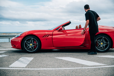 man getting into red sports car