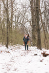 man gives woman a piggyback in the snowy woods