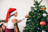 man helps toddler decorate christmas tree