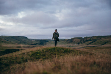 man hikes hilly landscape