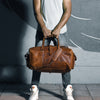 man holding his leather travel bag