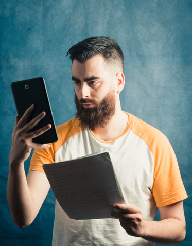 man holds a phone and a stack of white paper