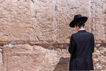man in black in front of wailing wall