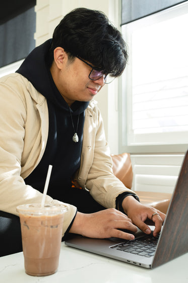 man in glasses types on a laptop beside iced coffee