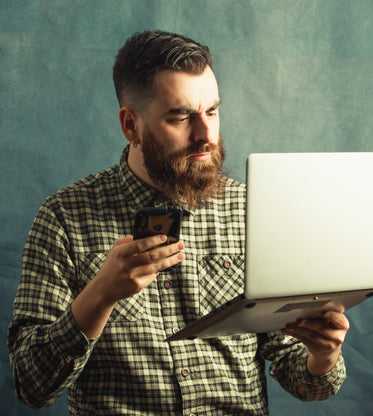 man in plaid holds a laptop and cellphone