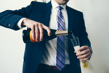 man in suit celebrates with champagne