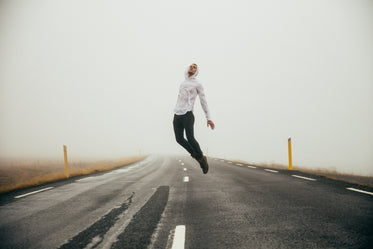 man jumping over highway