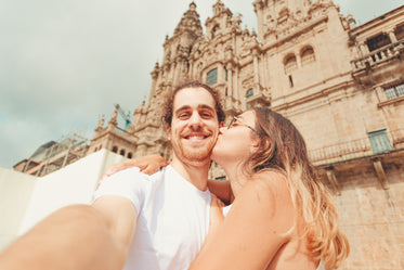 man kissed on the cheek while taking a selfie