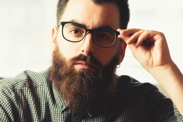 man looks at the camera as he adjusts his glasses