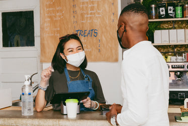 man orders coffee while wearing face mask