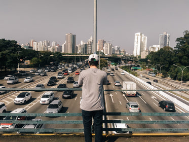 man overlooks highway bridge