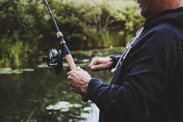 man reeling in on fishing rod