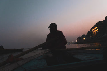 man rowing a boat at dusk