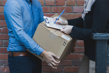 man signing for shipping box
