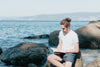 man sits on a rock by the water and reading his book