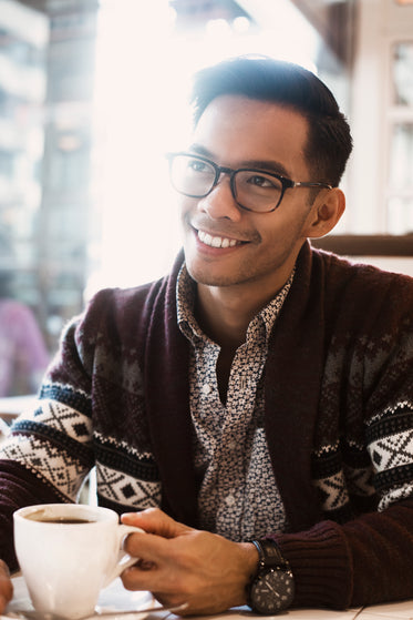 man smiles over coffee in cafe
