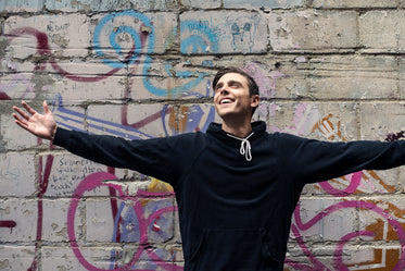 man smiles with open arms in city