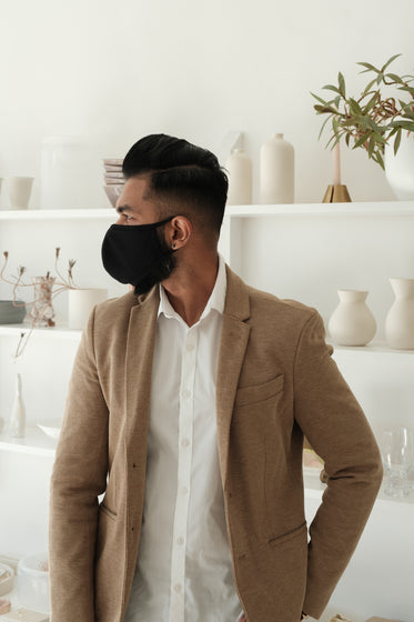 man standing in store wearing a black cloth face mask