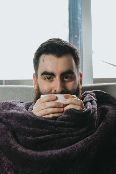 man wrapped in blanket and holding bowl close to his face