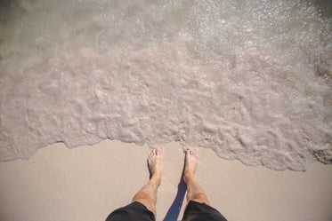 mans feet on ocean shore
