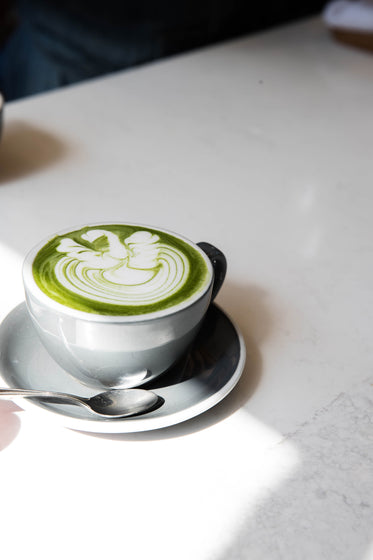 matcha latte in a grey mug on a white table