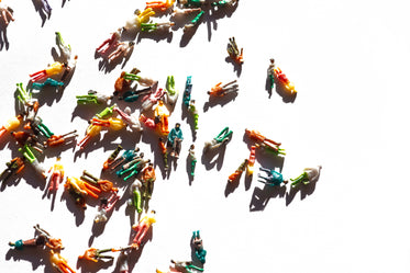 miniature figurines of people scattered on a white background