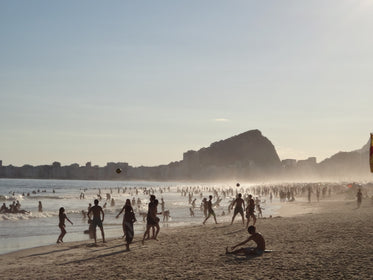misty crowded beach with hills and buildings