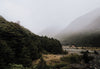 misty mountain valley and a huddle of woodland huts