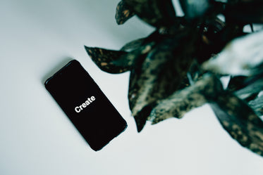 mobile phone shows the word create on a white table