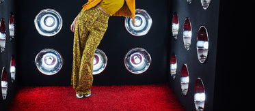 model leaning against a wall of lights atop red shag carpet