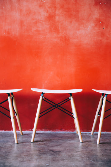 modern stools by red wall