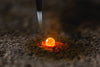molten metal drop on bed of ash