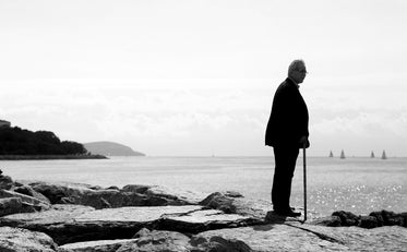 monochrome man standing alone looking beyond the shore