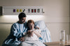 mother and father sitting in hospital bed admiring newborn