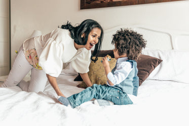 mother playing with son in bedroom