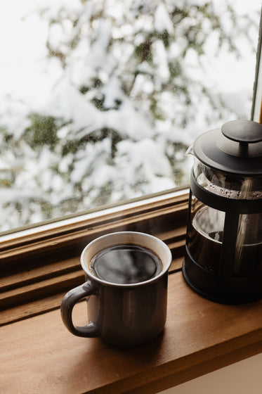 mug of coffee and a french press on a window sill