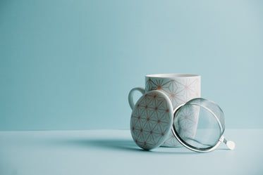 mug with a lid and strainer sits against a blue background