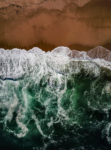 ocean waves meet red sands aerial