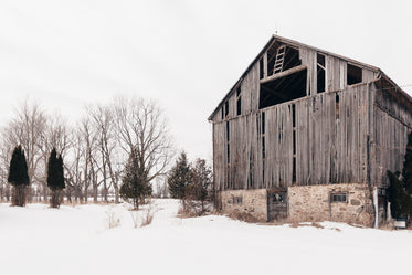 old barn with missing section surrounded by snow